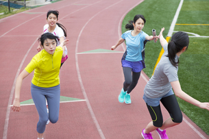 陸上競技場でバトンの手渡しをする女子学生たちの写真素材 [FYI02967375]