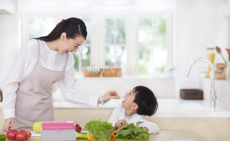 キッチンで子供に果物をあげる奥さんの写真素材 [FYI02967377]