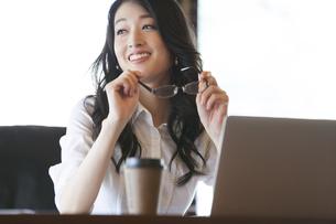 オフィスのデスクでくつろぐビジネス女性の写真素材 [FYI02967379]