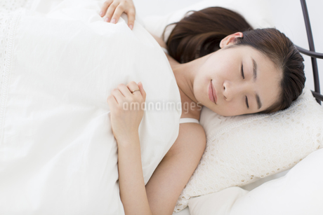 ベットで顔を横にして眠る女性の写真素材 [FYI02967380]