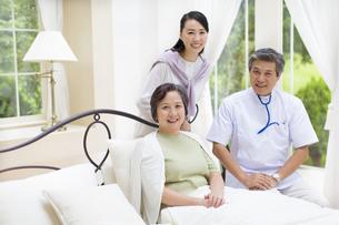 訪問医療の医者と笑顔の母と娘の写真素材 [FYI02967381]