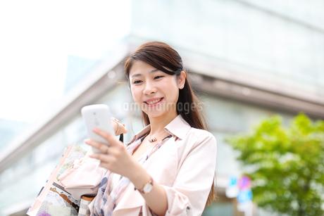 スマートフォンを見る買物中の女性の写真素材 [FYI02967383]