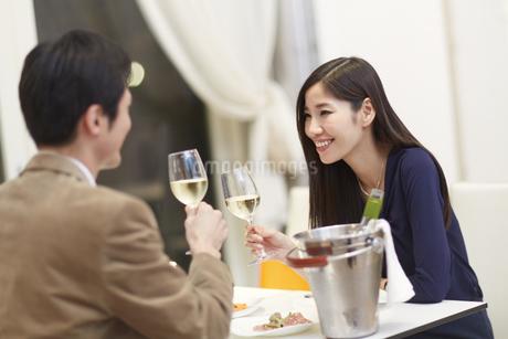 レストランでワインを手に語らうカップルの写真素材 [FYI02967384]