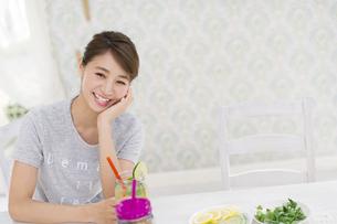椅子に座ってデトックスウォーターを持って笑う女性の写真素材 [FYI02967385]