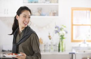 キッチンで料理を運ぶ笑顔の女性の写真素材 [FYI02967386]