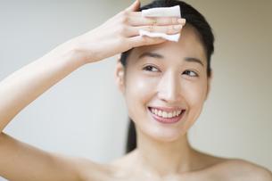 額にコットンをあてスキンケアをする女性の写真素材 [FYI02967387]