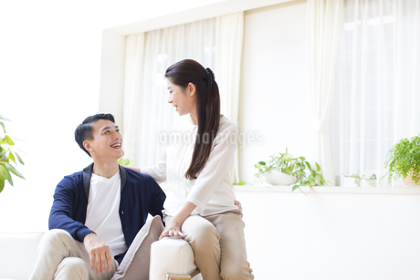 ソファーに掛けて笑い合う夫婦の写真素材 [FYI02967395]