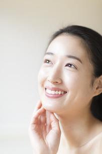 頬に片手を添えて上を見上げ微笑む女性の写真素材 [FYI02967399]