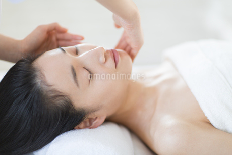 仰向けで顔をマッサージされている女性の写真素材 [FYI02967400]