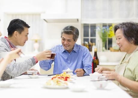 団欒の食卓で乾杯する父と息子の写真素材 [FYI02967406]