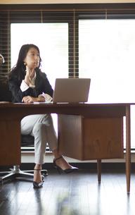 オフィスのデスクで考え込むビジネス女性の写真素材 [FYI02967407]