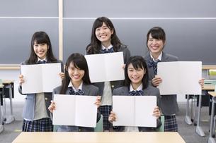 教室でノート開いて笑う女子高校生たちのポートレートの写真素材 [FYI02967408]
