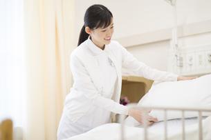 ベッドを綺麗にする女性看護師の写真素材 [FYI02967417]