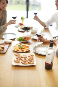 食事を前にワインで乾杯する三人の手の写真素材 [FYI02967419]