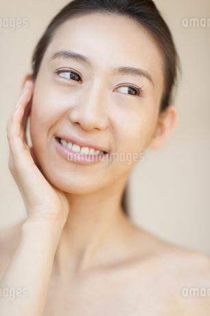 頬に片手を添えて微笑む女性の写真素材 [FYI02967420]