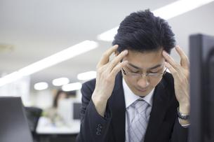 頭に手をやり下を向くビジネス男性の写真素材 [FYI02967424]