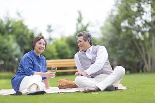 芝に腰かけて会話するシニア夫婦の写真素材 [FYI02967431]