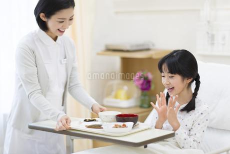 女の子に病院食を運ぶ女性看護師の写真素材 [FYI02967436]