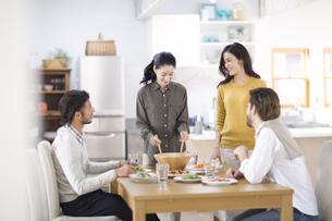 ダイニングテーブルで食事を楽しむ男性と女性たちの写真素材 [FYI02967437]