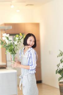 花を運びながら振り返る奥さんの写真素材 [FYI02967440]