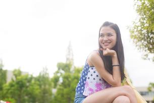 顎に手をあてて微笑む女子学生の写真素材 [FYI02967442]