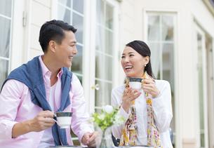 コーヒーカップを手に笑い合うカップルの写真素材 [FYI02967444]