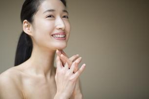 顎に両手を添えて微笑む女性の写真素材 [FYI02967446]