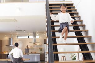 階段を駆け降りる女の子とダイニングにいる夫婦の写真素材 [FYI02967448]