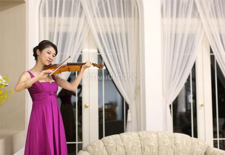 ドレスアップしてバイオリンを弾く女性の写真素材 [FYI02967449]