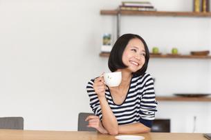 テーブルでカップを手に微笑む女性の写真素材 [FYI02967453]