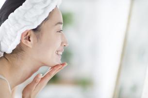 鏡の前でスキンケアをする微笑む女性の横顔の写真素材 [FYI02967455]