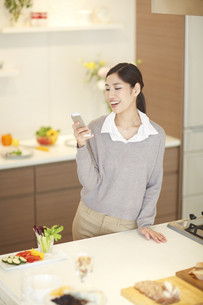 キッチンでスマートフォンを操作する女性見る女性の写真素材 [FYI02967456]