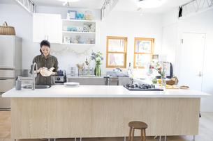 キッチンでコップを拭く女性の写真素材 [FYI02967457]