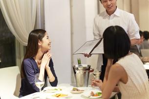 レストランで店員の話を聞く女性二人の写真素材 [FYI02967458]