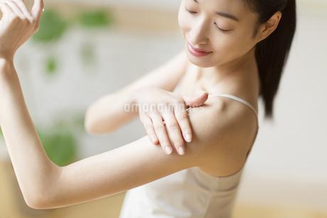 肩に手をあて微笑む女性の写真素材 [FYI02967460]