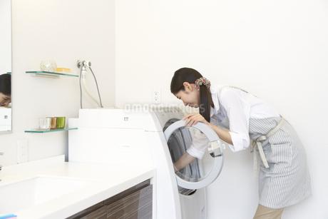 洗濯機から洗濯ものを取り出す主婦の写真素材 [FYI02967462]