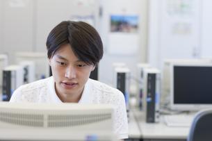 パソコン教室でモニターに向かう男子学生の写真素材 [FYI02967464]