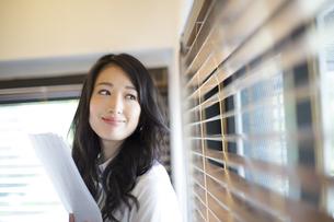オフィスの窓際で微笑むビジネス女性の写真素材 [FYI02967465]