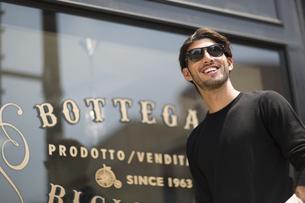 ウィンドウの前でサングラスをかけて微笑む男性の写真素材 [FYI02967468]