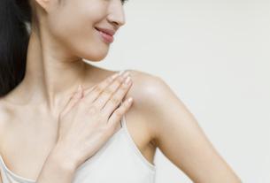 首もとに手をあてる女性の手元の写真素材 [FYI02967470]