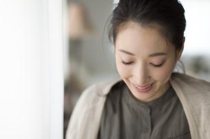 窓際でうつむく女性の写真素材 [FYI02967473]