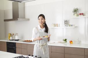 朝食をキッチンから運ぶ奥さんの写真素材 [FYI02967474]