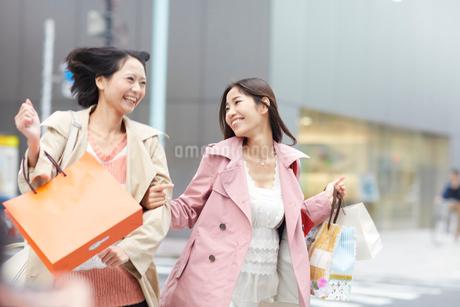 買い物中に手を組んで駆ける女性二人の写真素材 [FYI02967480]