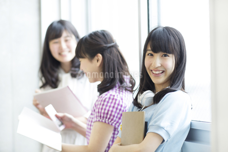 教室の窓際で教材を持って微笑む女子学生の写真素材 [FYI02967482]