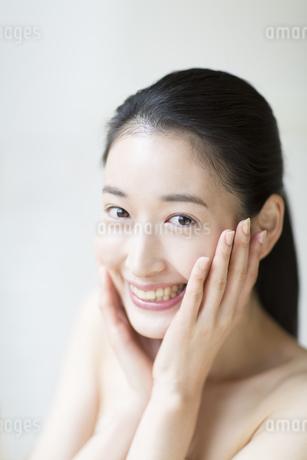頬に両手を添えた笑顔の女性の写真素材 [FYI02967487]