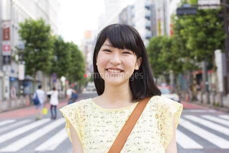 笑顔で道に立つ若い女性のアップの写真素材 [FYI02967488]
