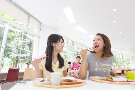 学食で食べるポーズをする女子学生の写真素材 [FYI02967493]