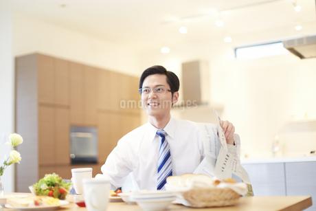 出勤前の朝食中に顔をあげて微笑む男性の写真素材 [FYI02967494]
