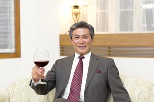 ワイングラスを手にポーズをとるシニア男性の写真素材 [FYI02967495]