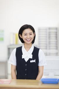 笑顔で受付をする女性の写真素材 [FYI02967496]